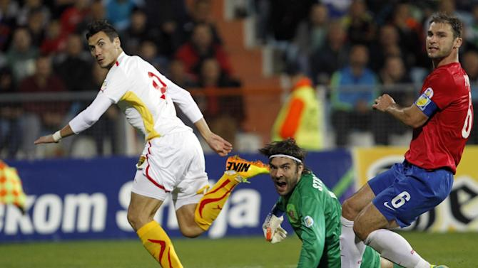 Macedonia's Adis Jahovic, left scores past Serbia's goalkeeper Vladimir Stojkovic, centre, and Branislav Ivanovic, right, during their World Cup 2014 Group A qualifying soccer match at the City Stadium in Jagodina, Serbia, Tuesday, Oct. 15, 2013