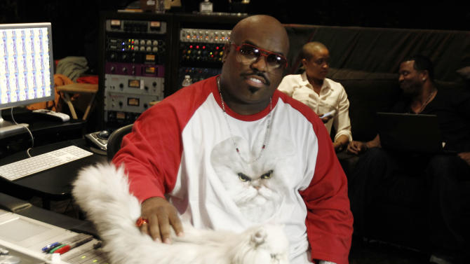 """In this May 2, 2012 photo, musician Cee-Lo Green and Purrfect the cat pose for a photo while working on the remix of the Meow Mix jingle in Los Angeles. Green, a judge on the singing competition series """"The Voice,"""" says he'll stick with the show """"as long as it's fresh."""" The rapper turned singer joined the show last year as coach and judge alongside Christina Aguilera, Blake Shelton and Adam Levine. (AP Photo/Matt Sayles)"""