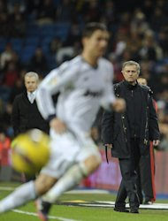 "Real Madrid's coach Jose Mourinho (R), pictured during their Spanish La Liga match against Espanyol, at the Santiago Bernabeu stadium in Madrid, on December 16, 2012. After defeats at Getafe, Sevilla and Betis, followed by the draw with Espanyol, Mourinho admitted the title was ""almost impossible now."""