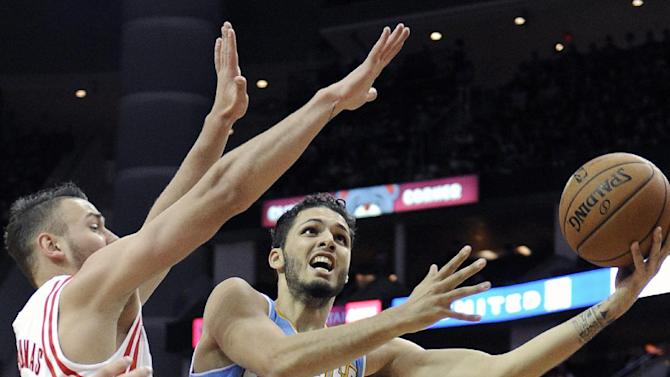 Denver Nuggets' Evan Fournier (94) tries a hook shot against the Houston Rockets' Donatas Motiejunas in the first half of an NBA basketball game Saturday, Nov. 16, 2013, in Houston