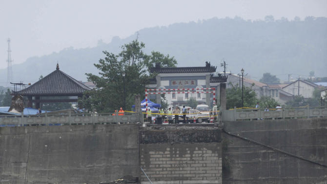 In this photo provided by China's Xinhua News Agency, a collapsed bridge over the Panjiang river is seen in Qinglian, Jiangyou city, southwest China's Sichuan Province, Tuesday, July 9, 2013. The official Xinhua News Agency said one sedan car, three minivans and one SUV fell into the torrent when the more than 40-year-old Qinglian bridge broke apart just before noon in the city. Three people were pulled from the raging river but six other remained missing following the bridge collapse Tuesday. (AP Photo/Xinhua, Li Qiaoqiao) NO SALES