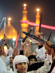 Shiite Muslims raise their swords outside the shrine of Imam Abbas in Karbala on Sunday. Provincial governor Amal al-Din al-Har told AFP that about three million pilgrims, including 200,000 from foreign countries, have come to Karbala for the rituals.
