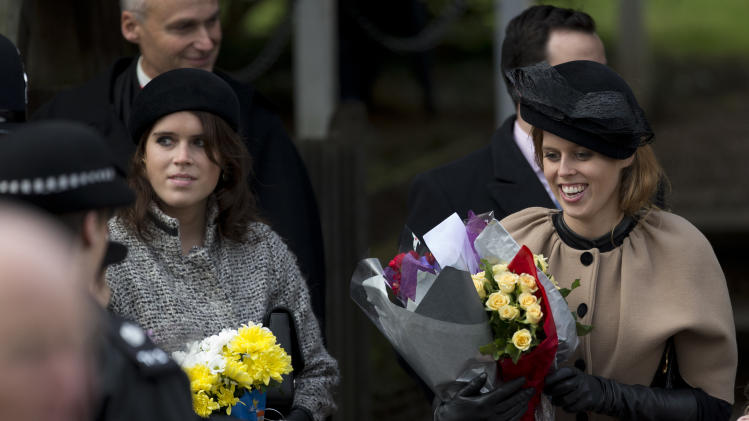 Britain's Queen Elizabeth II's granddaughters Princesses Beatrice, right, and Eugenie, left, hold flowers the Queen received from children after attending the British royal family's traditional Christmas Day church service in Sandringham, England, Tuesday, Dec. 25, 2012.  (AP Photo/Matt Dunham)