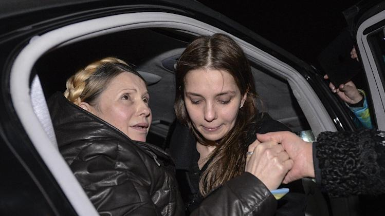 In this Saturday, Feb. 22, 2014 photo, former Ukrainian prime minister Yulia Tymoshenko is helped out of her car by her daughter Eugenia, right, upon her arrival to Kiev's iconic Independence Square to address the assembled crowd, following her surprise release from prison . (AP Photo/ Andrew Kravchenko, pool)