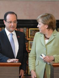 French President Francois Hollande and German Chancellor Angela Merkel chat at the end of a joint press conference at Villa Madama in Rome. The top four eurozone countries met in Rome on Friday to tackle the relentless debt crisis with France, Italy and Spain pressuring Germany to accept new growth and intervention measures. AFP PHOTO / ALBERTO PIZZOLI