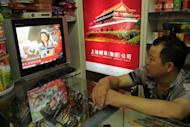 A shop owner watches television in Shanghai as China's first female astronaut Liu Yang is shown getting out of the return capsule of the Shenzhou-9 spacecraft after returning to earth on June 29, 2012. Three Chinese astronauts returned to Earth after achieving China's most complex and longest operations in orbit, major steps forward in the country's effort to build a space station