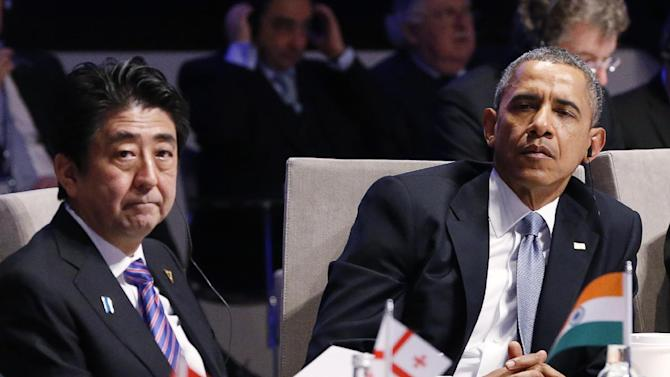 Japan's Prime Minister Shinzo Abe, left, and U.S. President Barack Obama, right, attend the opening session of the Nuclear Summit in The Hague, Netherlands, on Monday, March 24, 2014. Obama gathered with world leaders in a day of delicate diplomacy, as he sought to rally the international community Monday around efforts to isolate Russia following its incursion into Ukraine. Nuclear terrorism was the official topic as Obama and other world leaders streamed in to a convention center in The Hague for a two-day nuclear summit. But the real focus was on a hurriedly scheduled meeting of the Group of Seven industrialized economies to address the crisis in Ukraine on the sidelines of the nuclear summit. (AP Photo/Yves Herman, Pool)