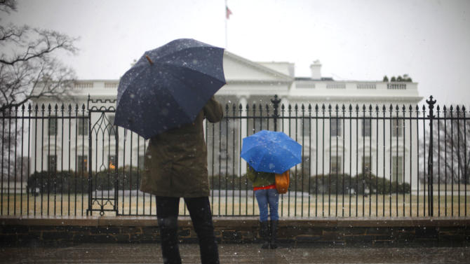 Snow falls on tourists stopping in front of the White House in Washington, Wednesday, March 6, 2013. Schools, businesses and the federal government closed in anticipation of a snow storm that could blanket the region. (AP Photo/Pablo Martinez Monsivais)