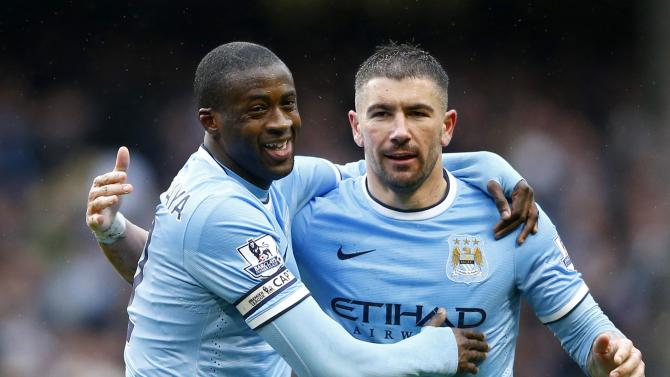 Manchester City's Toure celebrates with team mate Kolarov after scoring a third goal against Fulham during their English Premier League soccer match at the Etihad stadium in Manchester