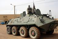 Movement for Oneness and Jihad in West Africa (MUJAO) fighters stand guard on a tank abandoned by the Malian Army near Gao airport in August 2012. Dozen of Algerian jihadists have arrived in the Malian city of Timbuktu to support armed Islamist groups who are imposing an increasingly brutal version of sharia law in the vast northern areas under their control, security sources said Sunday.