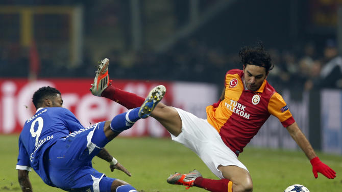 Galatasaray's Inan and Schalke 04's Bastos fall during their Champions League soccer match in Istanbul