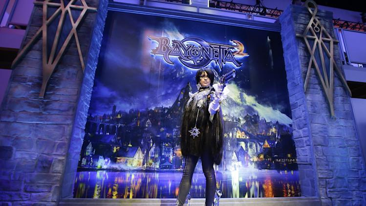 "A model dressed as Bayonetta, a video game character from the ""Bayonetta 2,"" poses for photos at the Nintendo booth during the Electronic Entertainment Expo in Los Angeles, Wednesday, June 12, 2013. (AP Photo/Jae C. Hong)"