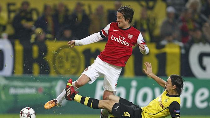 Dortmund's Neven Subotic, right, challenges Arsenal's Tomas Rosicky during the Champions League group F soccer match between Borussia Dortmund and Arsenal FC in Dortmund, Germany, Wednesday,Nov.6,2013