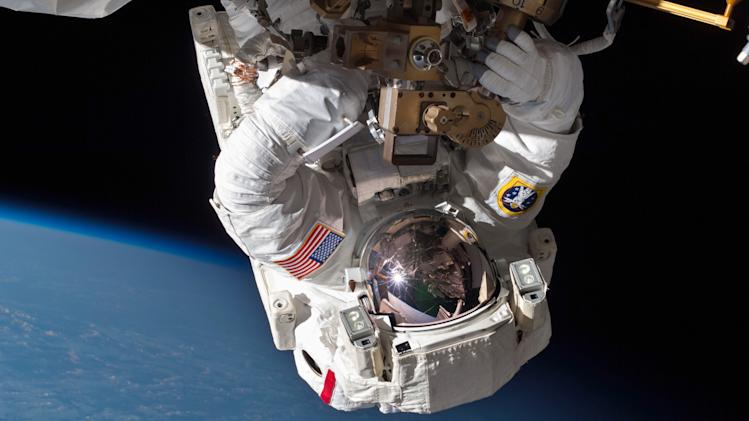 In this Saturday, May 11, 2013 photo made available by NASA, astronaut Chris Cassidy and Tom Marshburn, not pictured, perform a space walk to inspect and replace a pump controller box on the International Space Station after an ammonia coolant leak was discovered. (AP Photo/NASA)