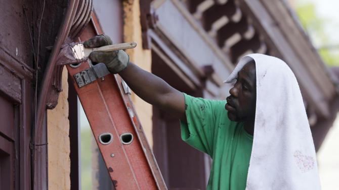 Vincent Davis of Albany wears a towel on his head to shield the heat while painting a house on Tuesday, July 16, 2013, in Albany, N.Y. (AP Photo/Mike Groll)