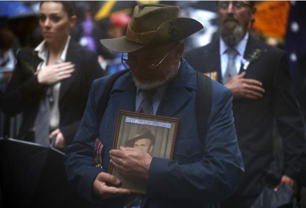 The relative of a veteran covers a photograph of him to stop the rain from falling on it as he participates in the annual ANZAC Day march through central Sydney