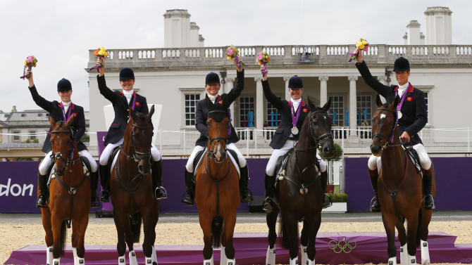Britain's team members pose on their horses after receiving their silver medals in the Eventing Team Jumping equestrian event victory ceremony at the London 2012 Olympic Games
