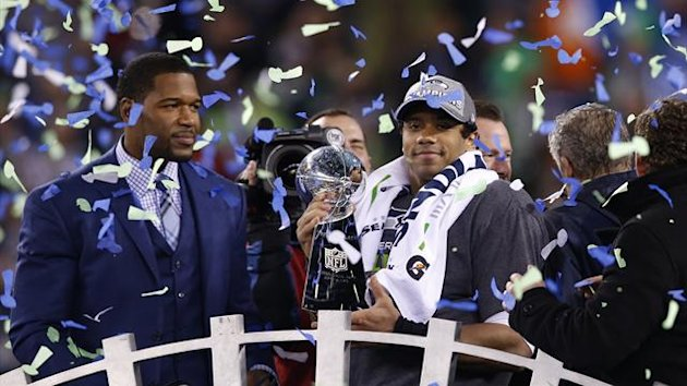 Seattle Seahawks quarterback Russell Wilson holds up the Vince Lombardi Trophy next to newly elected Hall of Fame player Michael Strahan (L) after the Seahawks defeated the Denver Broncos (Reuters)