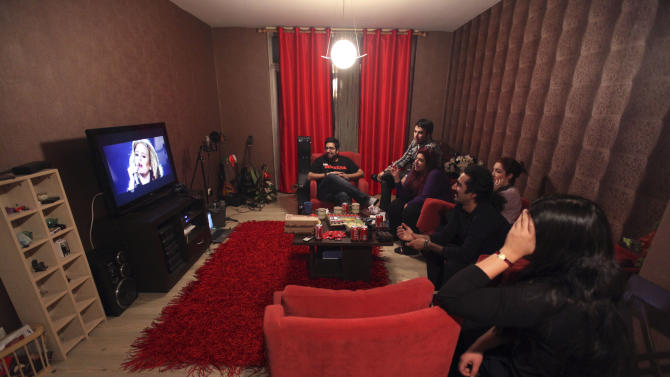 """In this picture taken on Monday, Feb. 4, 2013, members of an Iranian band called """"Accolade"""" and their friends watch a performance of British singer Adele, following their training session at the house of one of their members in Tehran, Iran. Headphone-wearing disc jockeys mixing beats. It's an underground music scene that is flourishing in Iran, despite government restrictions. (AP Photo/Vahid Salemi)"""