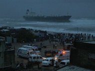 Ambulances and police vehicles are seen on the beachfront after the oil tanker ship Pratibha Cauvery ran aground off the coast in Chennai. Thousands of people evacuated from their homes in southeast India Wednesday as a cyclone slammed into the coast, killing two people, according to reports, and causing an oil tanker to run aground