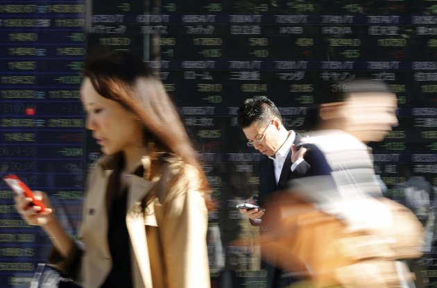 Pedestrians using their mobile phone walk past an electronic board in Tokyo. (Reuters)