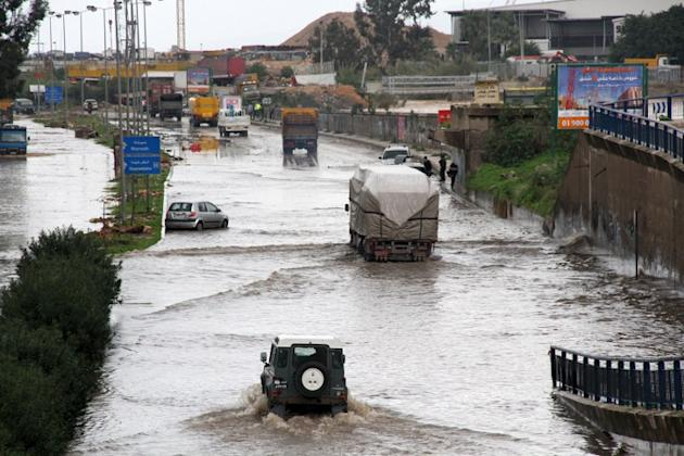 Cars drive through flood waters at the entrance of the Lebanese capital Beirut, on January 7, 2013, following a night of high winds and heavy rain fall.  AFP PHOTO/MIKE ITANI
