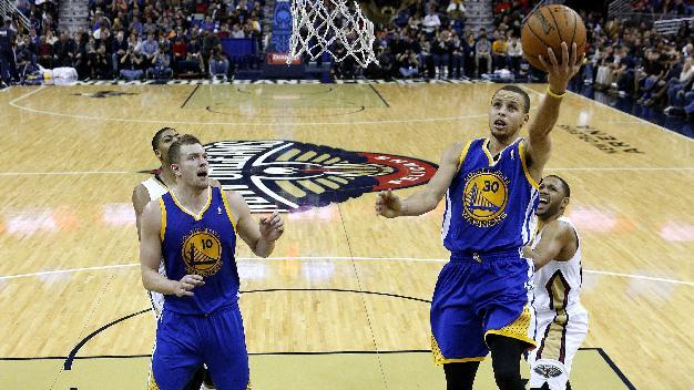 Golden State Warriors point guard Stephen Curry (30) drives to the basket past New Orleans Pelicans shooting guard Eric Gordon, right, during the second half of an NBA basketball game in New Orleans, Saturday, Jan. 18, 2014. The Warriors won 97-87