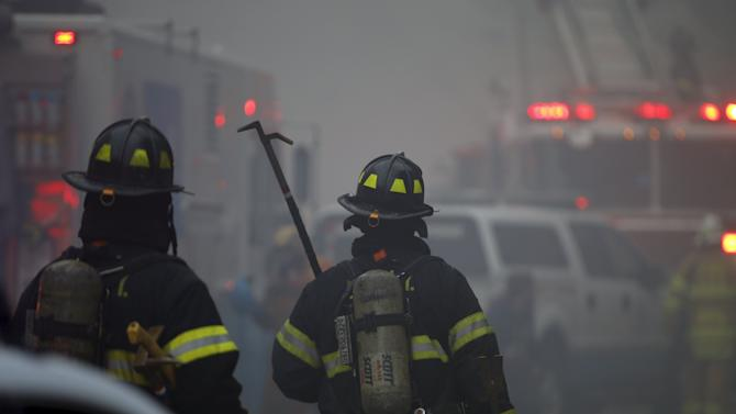 Firefighters walk towards the site of a residential apartment building collapse and fire in New York City's East Village neighborhood