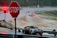 Floodwaters race across the Oxenford - Tamborine road on Australia's Gold Coast on January 28, 2013. Helicopters have plucked dozens of stranded Australians to safety in dramatic rooftop rescues as severe floods swept the northeast, killing four people and inundating thousands of homes