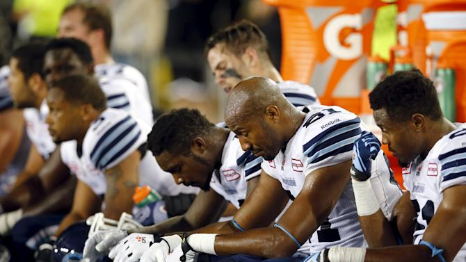 Toronto Argonauts players sit on the bench as their team plays against the Hamilton Tiger-Cats in their CFL football game in Hamilto