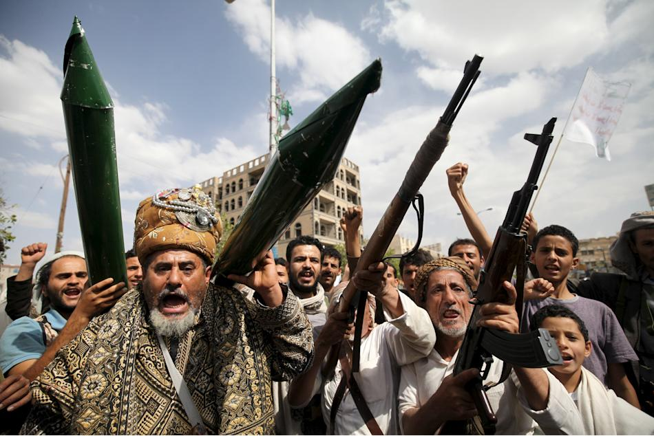 Houthi followers hold mock missiles and their rifles as they shout slogans during a demonstration against the United Nations in Sanaa