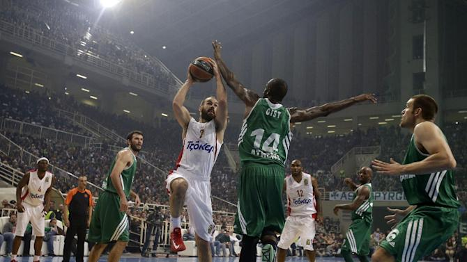 Panathinaikos' James Gist, 14, jumps to stops Olympiakos' Vassilis Spanoulis during their Euroleague basketball match of Top 16 at the Olympic Indoor Arena in Athens, Thursday, Feb. 20, 2014