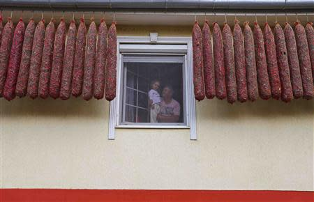 Paprika maker Matos holds his daughte at a window between hanging tubes of drying peppers in Batya