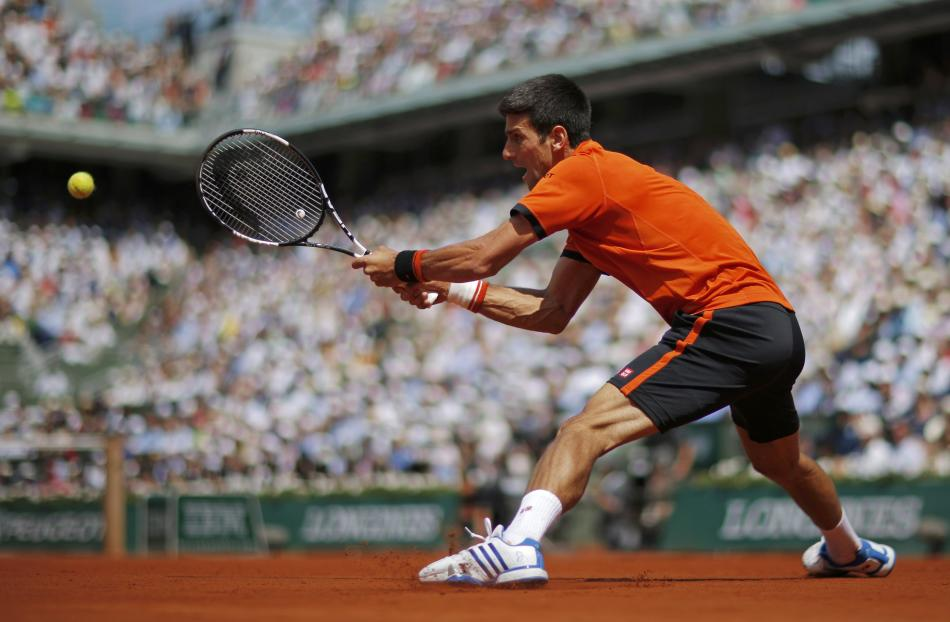 Novak Djokovic of Serbia returns the ball to Stan Wawrinka of Switzerland during their men's final match at the French Open tennis tournament at the Roland Garros stadium in Paris