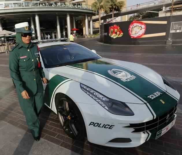 An Emirati female police officer poses near a Ferrari police vehicle on April 25, 2013 in the Gulf emirate of Dubai. Dubai police showed off a new Ferrari they will use to patrol the city state, hot o