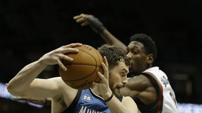 Minnesota Timberwolves' Kevin Love(42) grabs a rebound in front of Milwaukee Bucks' Larry Sanders, right, during the second half of an NBA basketball game, Saturday, Dec. 28, 2013, in Milwaukee
