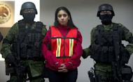 "Mexican Army soldiers guard Irasema Lopez Garza, partner of Carlos Oliva Castillo, aka ""La Rana"", alleged leader of the Zetas in the states of Coahuila, Nuevo Leon y Tamaulipas, in Mexico City, in 2011. The high mortality rate in Mexico's drug war has seen women progress quickly in the shadowy underworld of the cartels and they are increasingly taking on key management roles, a new book says"