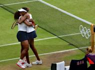 Venus (right) and Serena Williams celebrate after winning the women's doubles final. The sisters became the first tennis players to win four Olympic golds on Sunday after a 6-4, 6-4 victory over Czech pair Andrea Hlavackova and Lucie Hradecka in the women's doubles final at Wimbledon