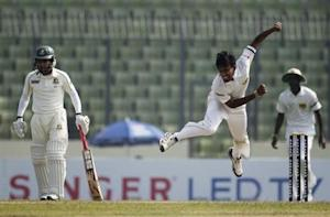 Sri Lanka's Suranga Lakmal bowls as Bangladesh's captain Mushfiqur Rahim (L) watches during the first day of their first test cricket match of the series in Dhaka January 27, 2014. REUTERS/Andrew Biraj