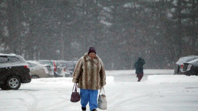 State employees walk through the snow as they get ready to drive home as snow falls Tuesday, Dec. 17, 2013, in Concord, N.H. Up to 6-inches of snow is expected in New England. (AP Photo/Jim Cole)