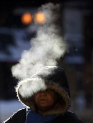 A woman walks in frigid cold temperatures though downtown Chicago, Illinois, January 6, 2014. REUTERS/Jim Young