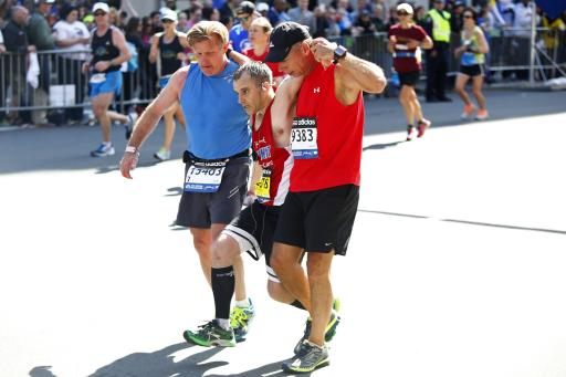 Adam Hurst is assisted by Jim Grove (L) and David Meyer down Boylston Street during the 118th running of the Boston Marathon in Boston, Massachusetts April 21, 2014. REUTERS/Dominick Reuter
