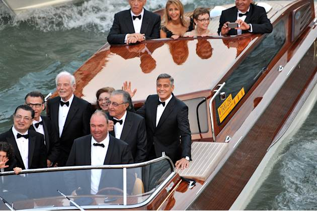 Actor George Clooney, right, waves from a boat with, from left, his father Nick Clooney, his sister Adelia Zeidler, and Ramzi Alamuddin, father of her fiancee Amal Alamuddin, on their way to the Aman