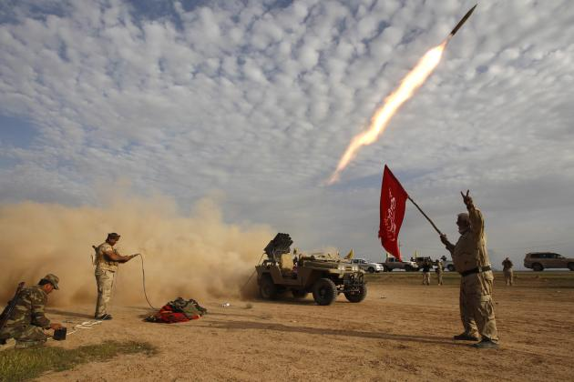 Shi'ite fighters launch a rocket during clashes with Islamic State militants on the outskirts of al-Alam