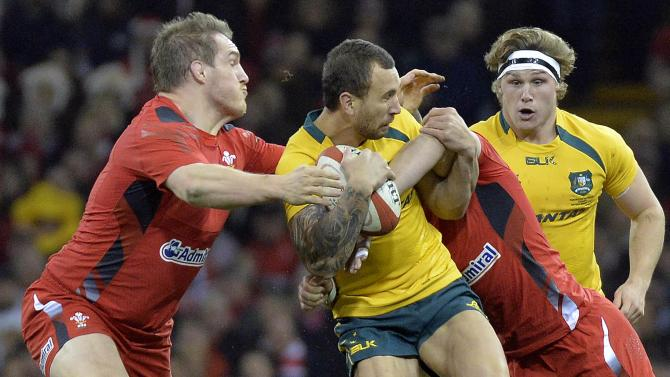 Australia's Quade Cooper is tackled as he tries to break through the Welsh ranks during their international rugby union match in Cardiff