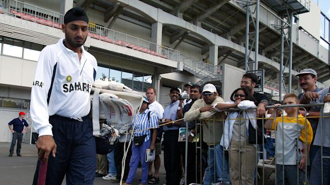 Indian spin bowler Harbhajan Singh walks past fans