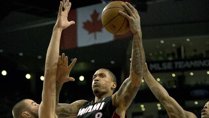 Miami Heat forward Michael Beasley (8) drives to the hoop past Toronto Raptors center Jonas Valanciunas during the first half of an NBA basketball game, Tuesday, Nov. 5, 2013 in Toronto