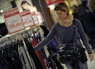 A woman looks at a dress in a shop in Barcelona. Spanish retail sales fell 9.8% in April from March, the biggest monthly drop since the statistical series began in 2003, the national statistics institute says