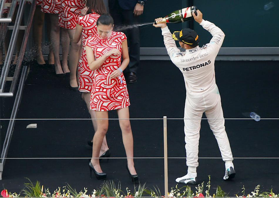 Mercedes Formula One driver Hamilton of Britain sprays champagne at a grid girl as he celebrates his victory on the podium after the Chinese F1 Grand Prix at the Shanghai International Circuit