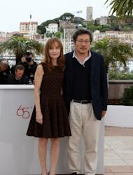 """South Korean director Hong Sangsoo and French actress Isabelle Huppert pose during the photocall of """"Da-Reun Na-Ra-E-Suh"""" (In Another Country). Hong, 51, is a Cannes regular, now on his fourth turn in competition after """"Woman is the Future of Man"""" and """"Tale of Cinema"""" in 2004 and 2005, then """"Night and Day"""" in 2008"""